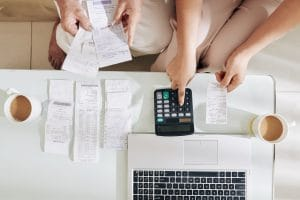Adult daughter helping senior mother with bookkeeping and analyzing finances