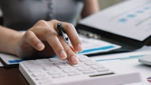 Close up accountant banker or bookkeeper making calculations with calculator. Savings, finances and economy concept