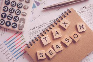 Alphabet letter wooden blocks tiles Tax season with on U.S. tax form