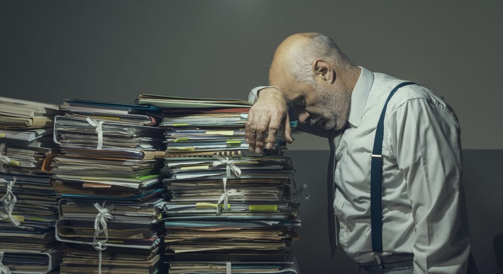 Stressed sad business executive overloaded with piles of paperwork, bureaucracy, taxes and deadlines concept